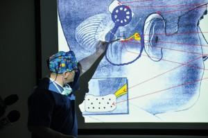 Konferencja prasowa. Prof. Henryk Skarżyński oraz dr hab. Artur Lorens, kierownik Zakładu Implantów i Percepcji Słuchowej Instytutu, wyjaśniają dziennikarzom, na czym polega trudność wszczepienia implantu do pnia mózgu.
