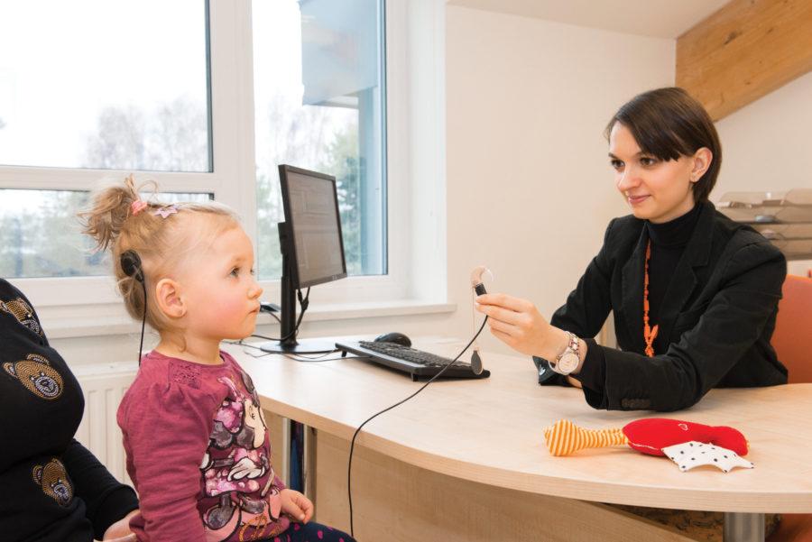 Mgr Marika Kruszyńska, logopeda, sprawdza reakcje dziecka na dźwięki.